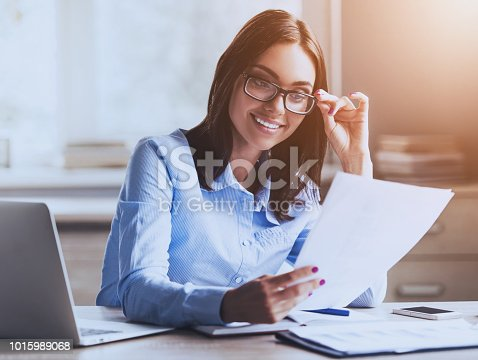 istock Young Pretty Lady Reading Documents and Smiling. 1015989068