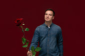 Young pretty man holding one red rose to give to his beloved. Making present to girlfriends in St. Valentines day. Being romantic