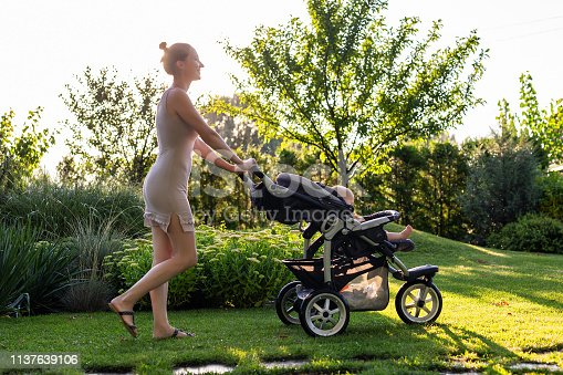 Young pretty mother with baby in stroller enjoying walking in green fresh garden at sunset. Mom having fun with baby in pram in beautiful park. Happy motherhood concept.