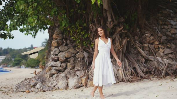 junge hübsche lächeln, die frau mit langen haaren in weißen drees an einem tropischen strand spaziergänge - drees und sommer stock-fotos und bilder