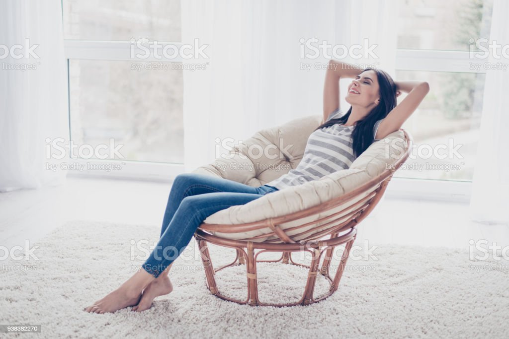 Young pretty smiling lady sitting on the armchair having a rest and dreaming with closed eyes stock photo