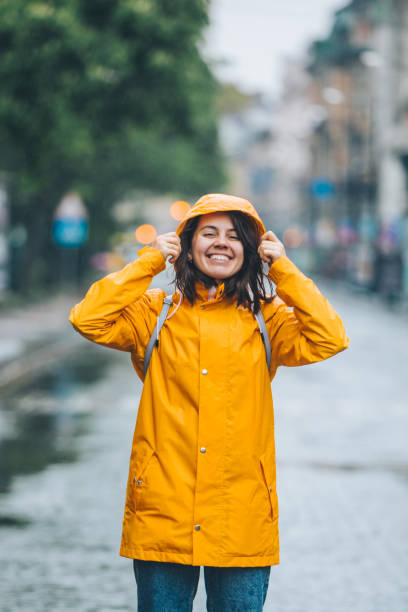 young pretty smiling woman portrait in raincoat with hood stock photo