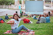 istock young pretty smiling woman sitting on blanket with popcorn and drink ready to watch movie 1259904231