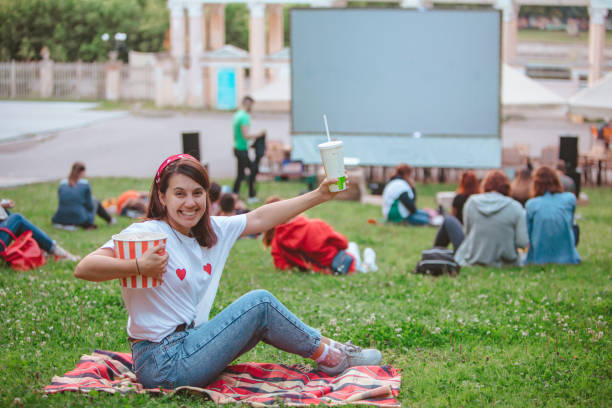 young pretty smiling woman sitting on blanket with popcorn and drink ready to watch movie stock photo