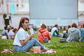 istock young pretty smiling woman sitting on blanket with popcorn and drink ready to watch movie 1267093724