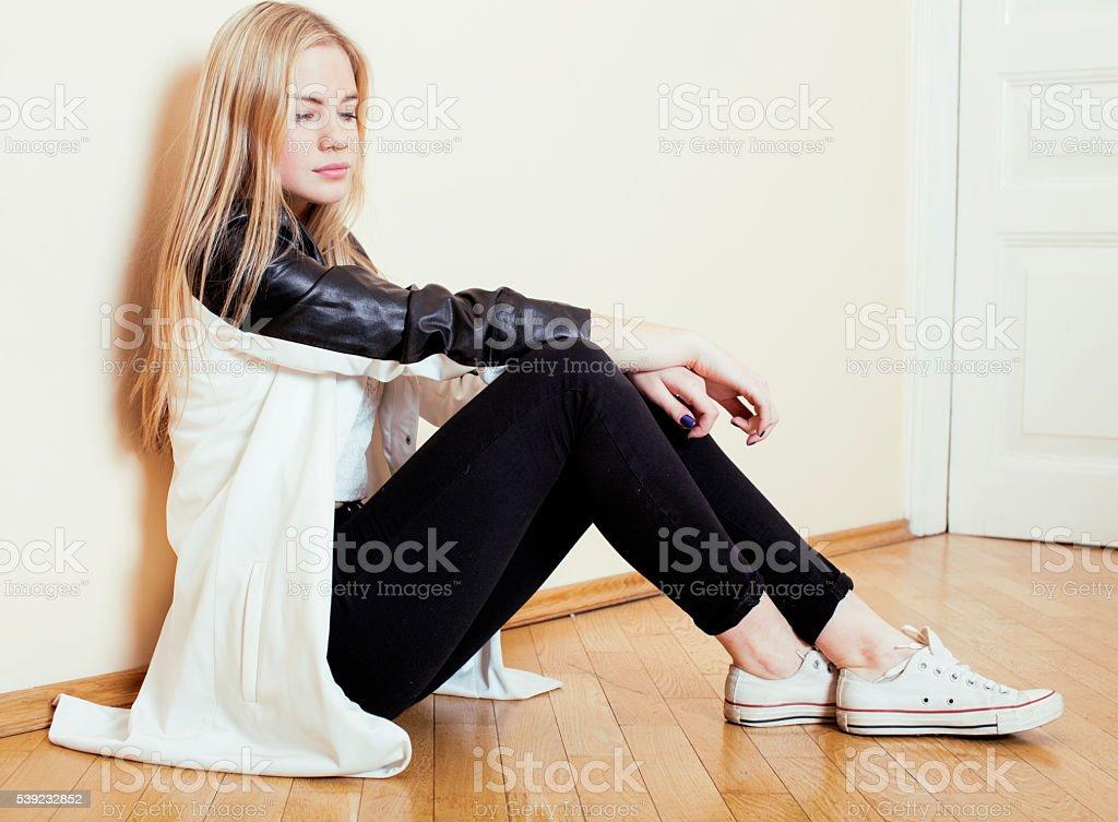 Jovem adolescente loira linda garota sentada no chão em casa foto royalty-free