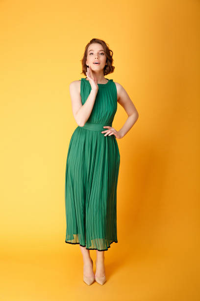 1c4355eb3b34 young pretty woman akimbo in green dress looking at camera isolated on orange  stock photo