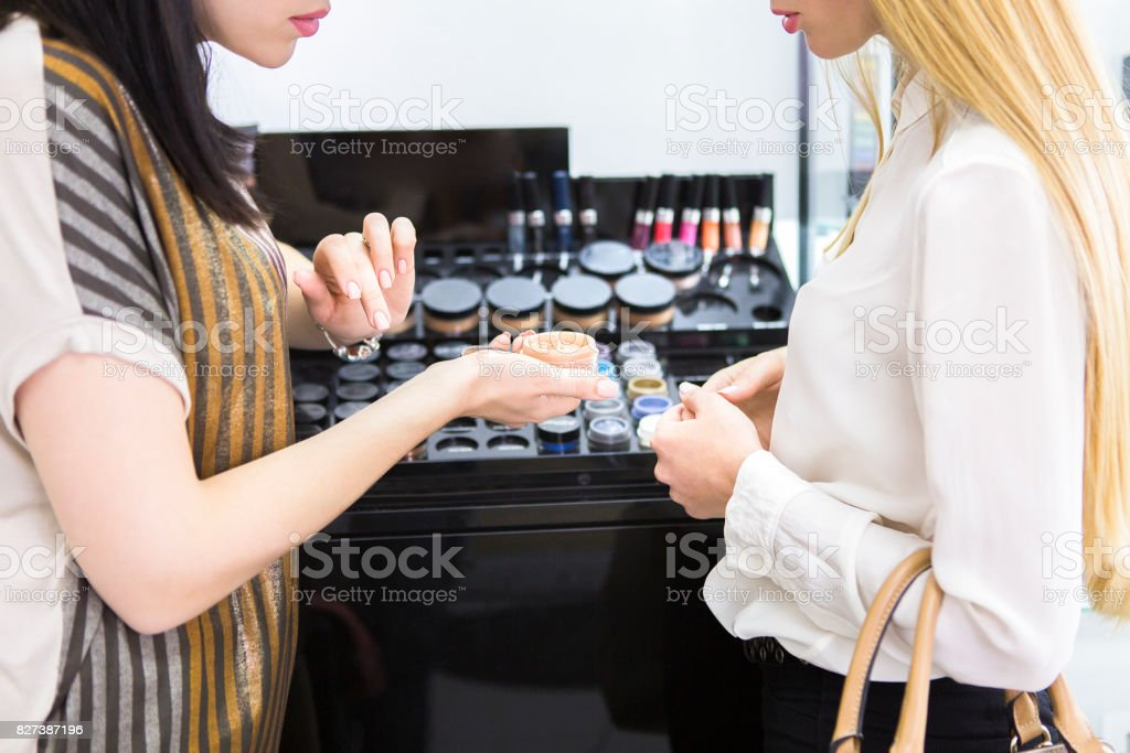 Young pretty woman and beauty consultant in shop stock photo
