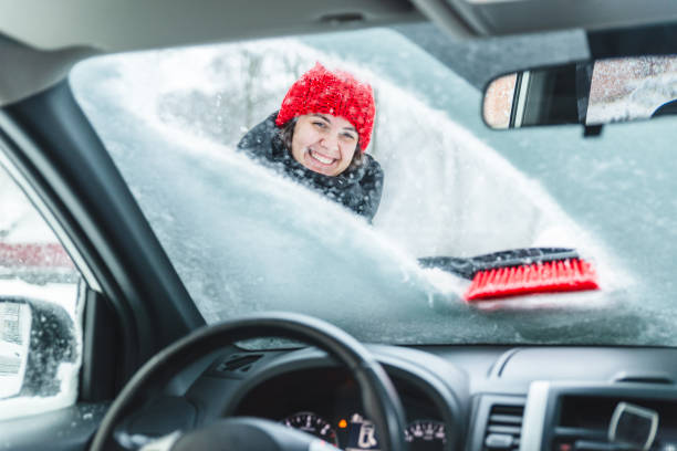 young pretty woman cleaning car after snow storm stock photo