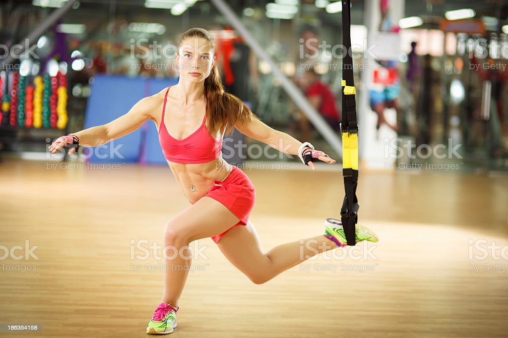 Young pretty woman doing crossover reverse lunge with trx straps stock photo