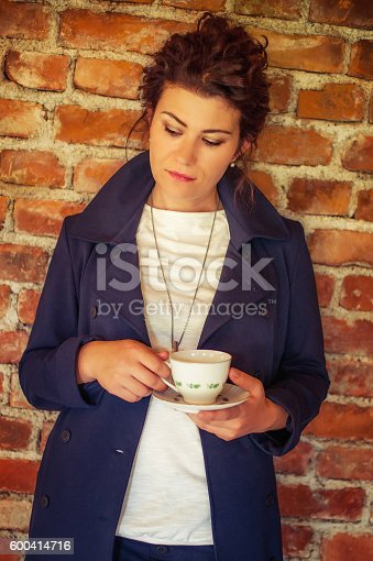 1078505838 istock photo Young pretty woman drinking coffee 600414716