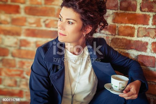 1078505838 istock photo Young pretty woman drinking coffee 600414788