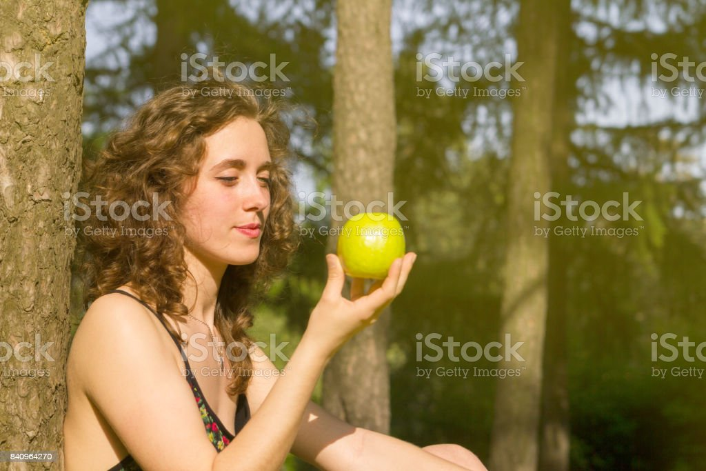 Young pretty woman eating apple on a field stock photo