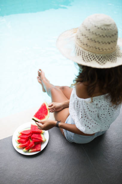 Young Pretty Woman Eating Watermelon on Pool Edge stock photo