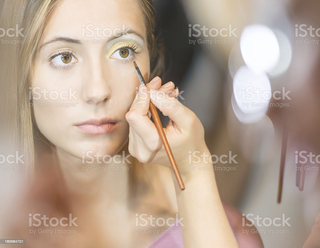 Young pretty woman getting make-up with brush. royalty-free stock photo