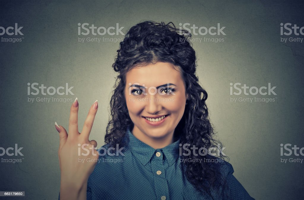 young pretty woman giving a three fingers sign gesture stock photo