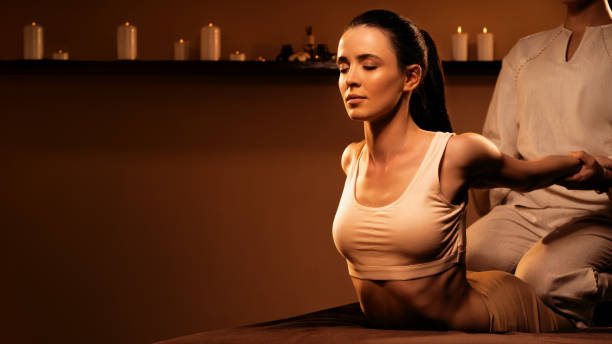 Young pretty woman has Thai massage at luxury spa. Warm inviting colors, calm atmosphere, charming light. stock photo