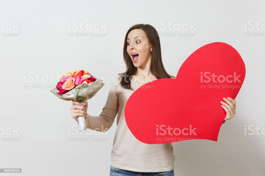 Young pretty woman holding big red heart, bouquet of beautiful roses flowers on white background. Copy space for advertisement. Place for text. St. Valentine's Day or International Women's Day concept stock photo