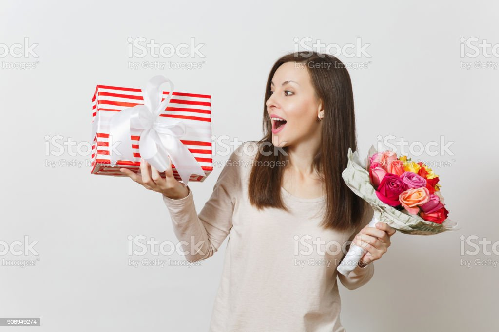 Young pretty woman holding bouquet of beautiful roses flowers, present box with gift isolated on white background. Copy space for advertisement. St. Valentines Day or International Women's Day concept stock photo