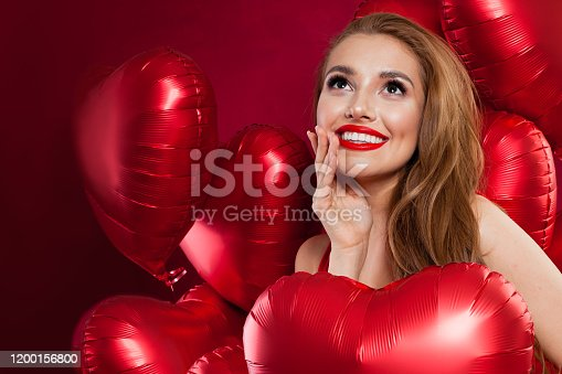 Young pretty woman holding red balloons. Birthday, Valentine's day, celebration and holiday background