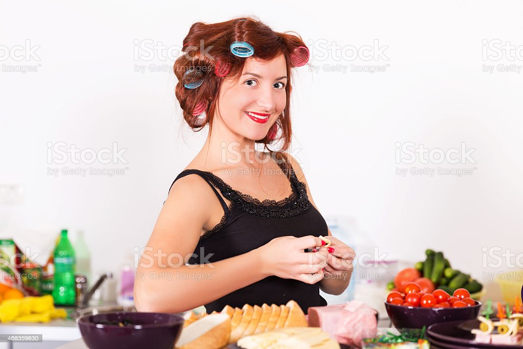 Young pretty woman housewife cooking with curlers hair royalty-free stock photo