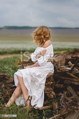 Young bride in a white wedding dress with curly blond hair, spends time alone, sitting in the open air in the summer in the countryside.Woman enjoying the beauty of blooming yellow sunflower in the summer in the countryside.