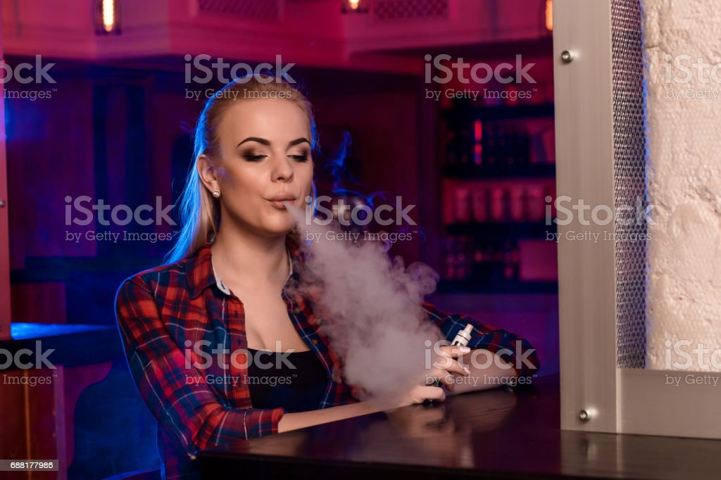Young pretty woman in a shirt in a cage smoke an electronic cigarette at the vape bar stock photo