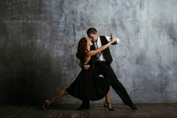 Young pretty woman in black dress and man dance tango stock photo