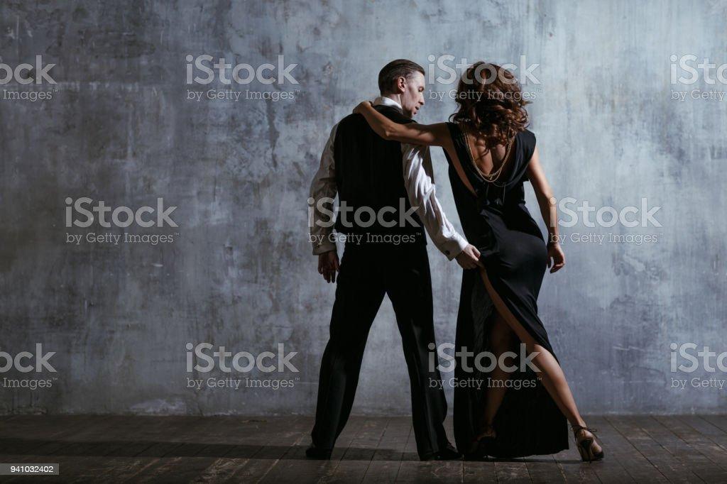 c27d7a519398 Ung vacker kvinna i svart klänning och mannen Dans tango royaltyfri  bildbanksbilder