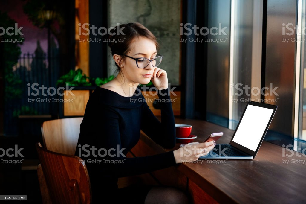 Young pretty woman in glasses works on a laptop, uses a smartphone, a freelancer, a computer, financial analyst, a sales manager. Copy space for your text on laptop screen. - Royalty-free Adult Stock Photo