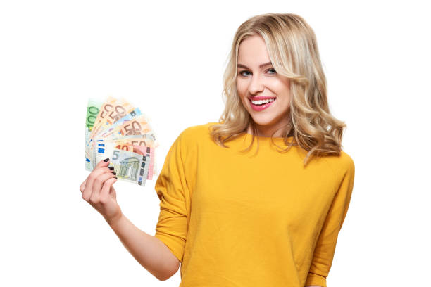 Junge hübsche Frau im gelben Pullover hält Haufen Euro-Banknoten, schaut in die Kamera und lächelt, isoliert auf weißem Hintergrund. – Foto