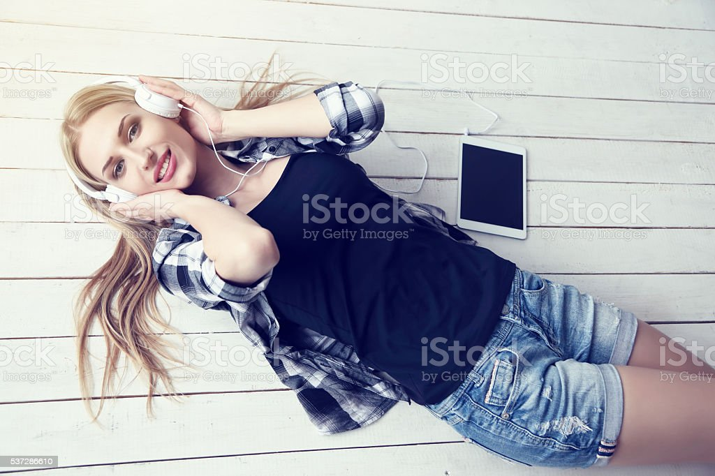 young pretty woman listening music in headphones stock photo