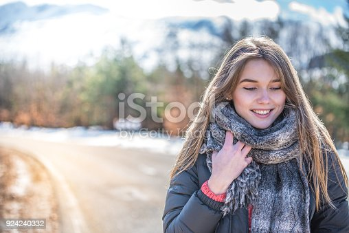 1051172208 istock photo Young pretty woman on a road with snow in winter 924240332