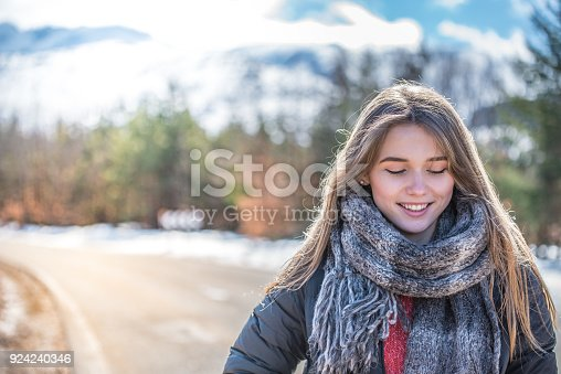 istock Young pretty woman on a road with snow in winter 924240346