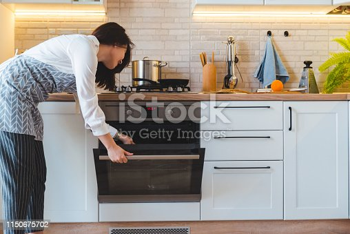 young pretty woman open oven to cook. domestic kitchen concept. copy space
