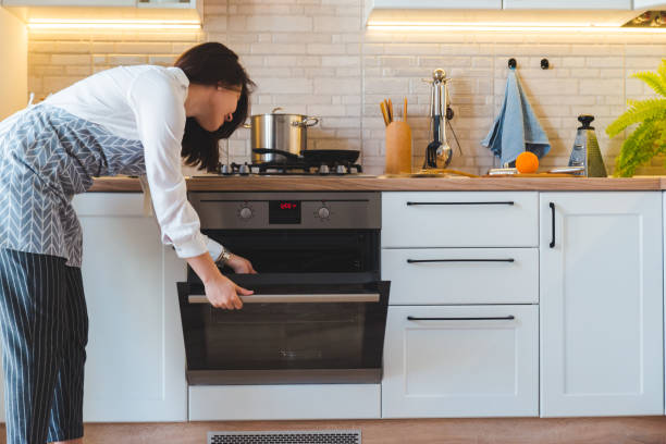 young pretty woman open oven to cook. domestic kitchen concept stock photo