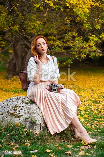 Pretty girl with red hair and vintage clothes, posing with a retro camera in a woods.