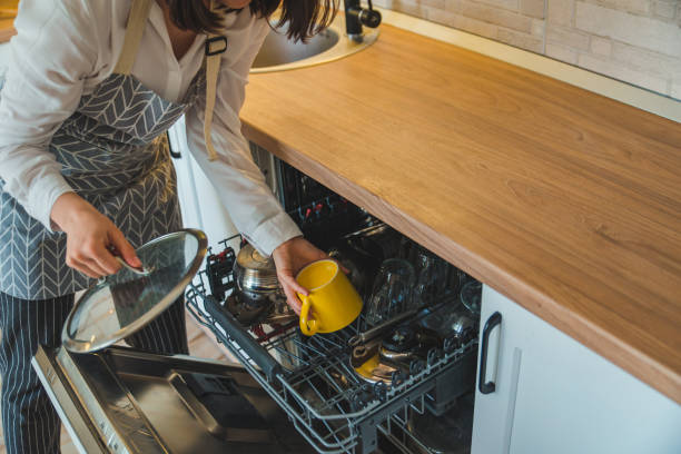 young pretty woman putting dishes in dishwasher young pretty woman putting dishes in dishwasher. domestic lifestyle dishwasher stock pictures, royalty-free photos & images