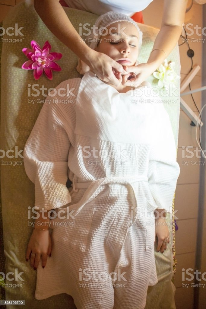 Young pretty woman receiving treatments in beauty salons. Young beautiful dark-haired woman in the office beautician lying on the couch. stock photo