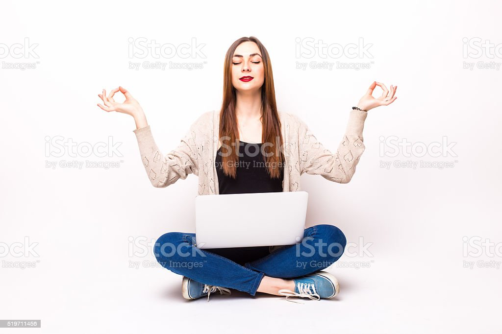 Young pretty woman sitting in lotus posture with laptop stock photo
