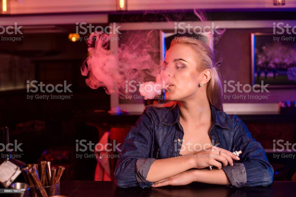 Young pretty woman smoke an electronic cigarette at the vape bar stock photo