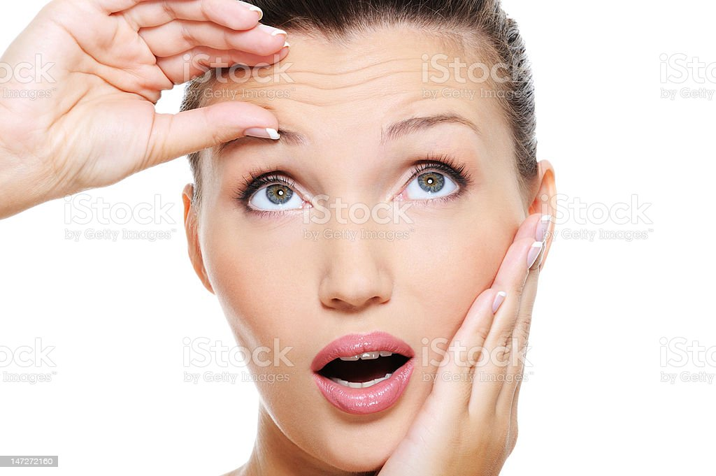 young pretty woman squeeze skin on forehead stock photo