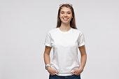 istock Young pretty woman standing with hands in pockets, wearing blank white t-shirt with copy space for your logo or text, isolated on gray background 1153003810