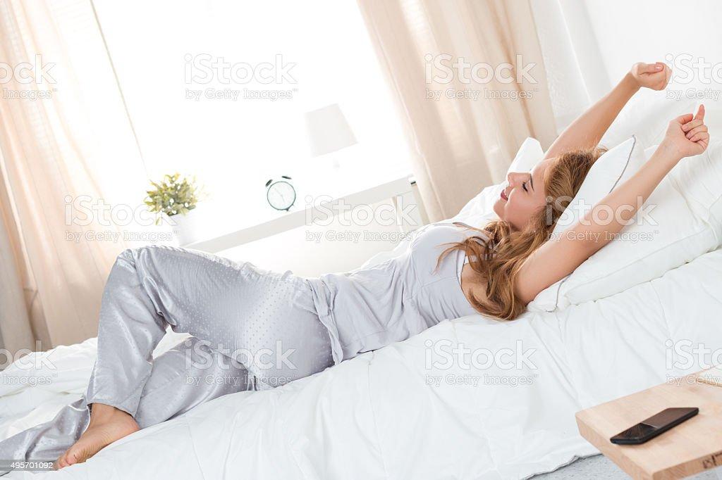 Jovem bela mulher se estende-se colocar na cama - foto de acervo