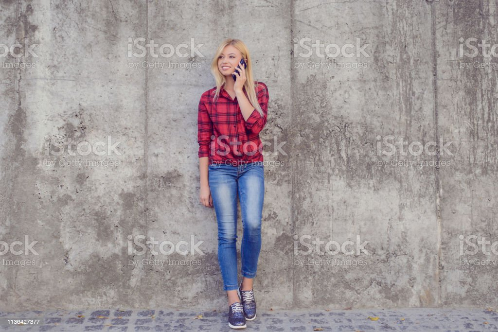 Young pretty woman talking on mobile phone while having a walk in a...