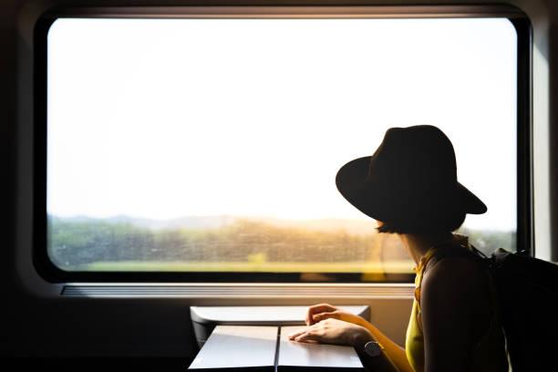 jeune jolie femme voyageant seule en train regardant la vue par la fenêtre. - train photos et images de collection