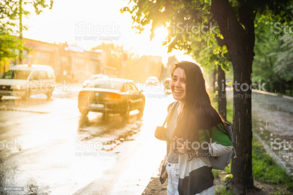 young pretty woman under the rain on sunset stock photo