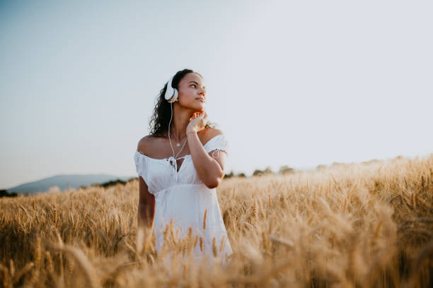 Young pretty woman walks in the cornfield while enjoying sunset stock photo