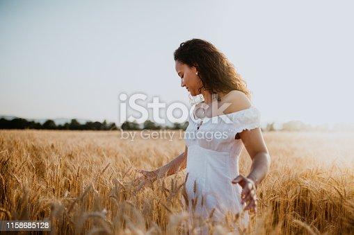 Junge Hübsche Frau genießt Sonnenuntergang im Kornfeld