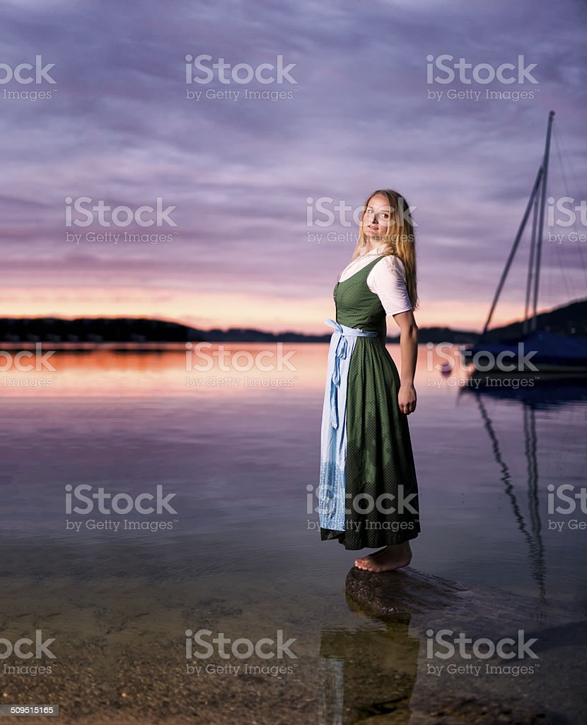 Young Pretty Woman Wearing a Traditional Dirndl at a Lake stock photo
